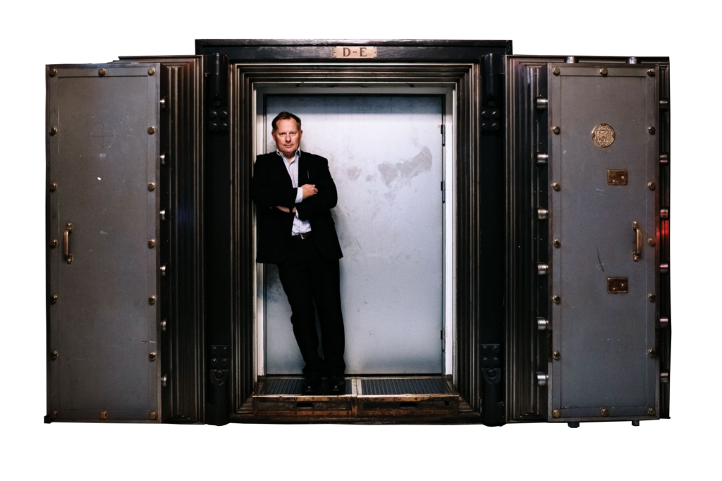 Image of Svein Harald Øygard standing in front of a bank vault